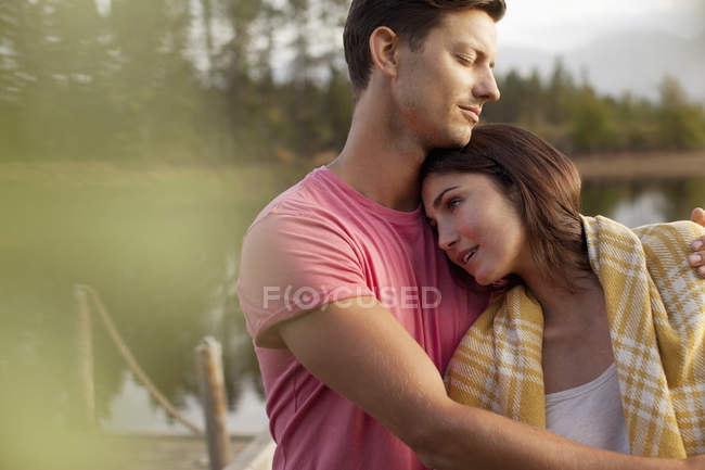 Serene couple hugging at lakeside — Stock Photo