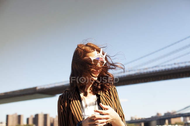 Femme en nouveauté lunettes de soleil par paysage urbain — Photo de stock