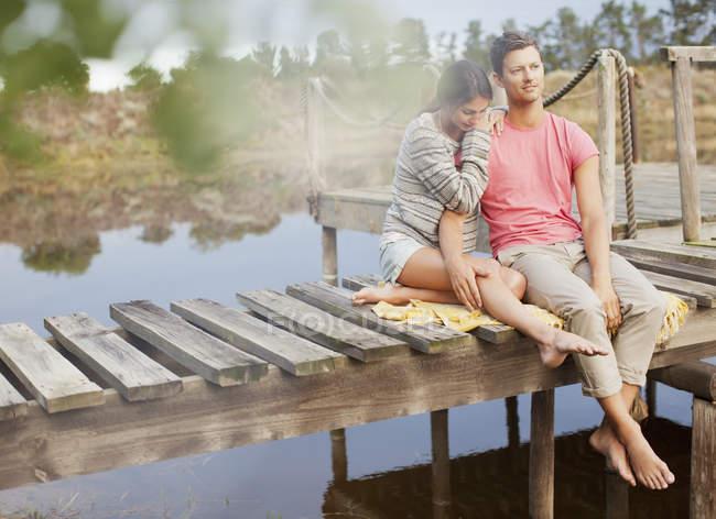 Serene couple siting on dock over lake — Stock Photo