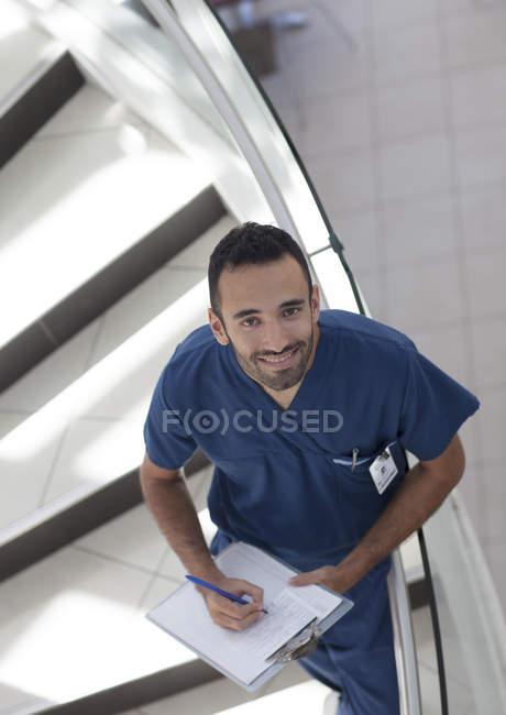 Enfermera en portapapeles en pasos, vista de ángulo alto - foto de stock