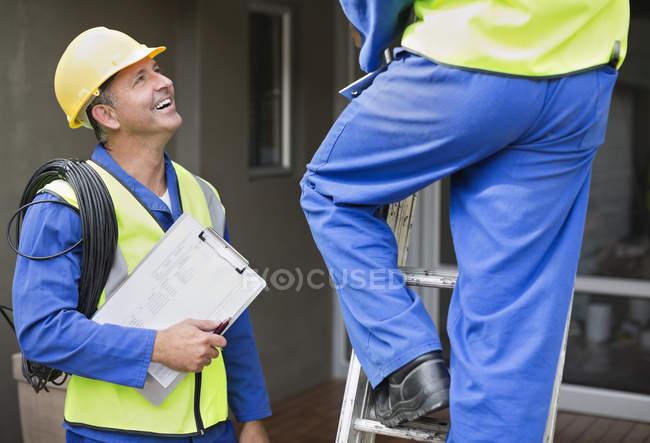 Умелые кавказские рабочие разговаривают на месте — стоковое фото