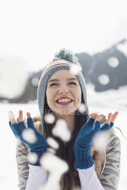 Счастливая женщина смотрит как падает снег — стоковое фото