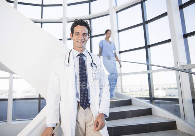 Portrait of smiling doctor on staircase in hospital — Stock Photo