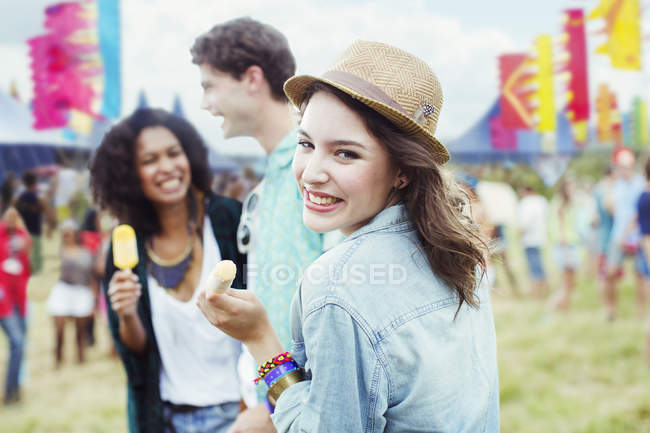 Portrait of woman eating flavored ice with friends at music festival — Stock Photo