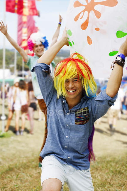 Playful men cheering in wigs at music festival — Stock Photo