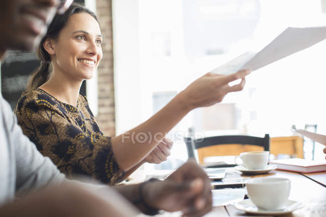 Businesswoman sharing documents at meeting in cafe — Stock Photo