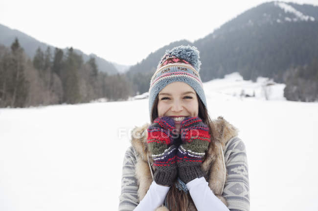 Portrait de femme enthousiaste portant tricot bonnet et gants en champ neigeux — Photo de stock