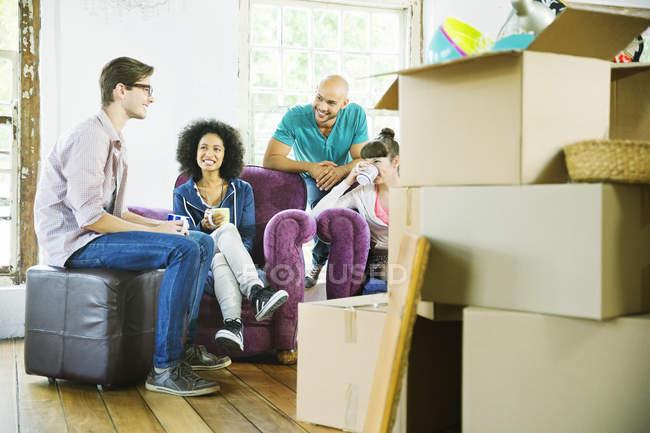 Amigos relaxando juntos em uma nova casa — Fotografia de Stock