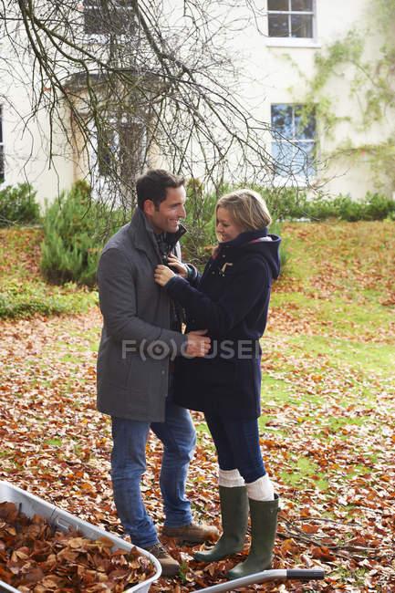 Casal sorridente em pé cara a cara nas folhas de outono — Fotografia de Stock
