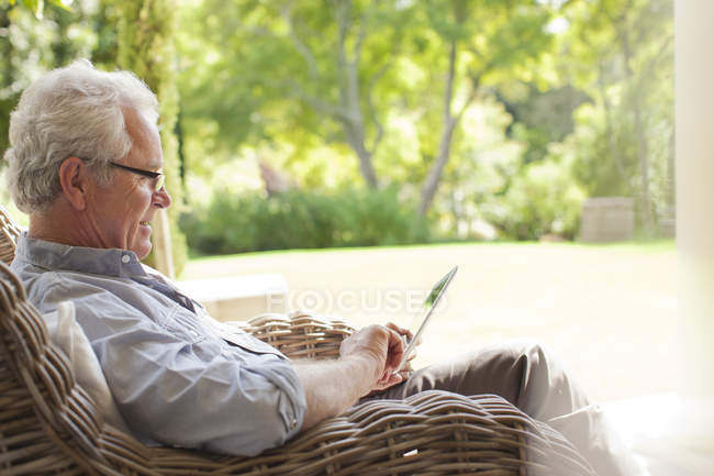 Senior man using digital tablet in wicker armchair on porch — Stock Photo
