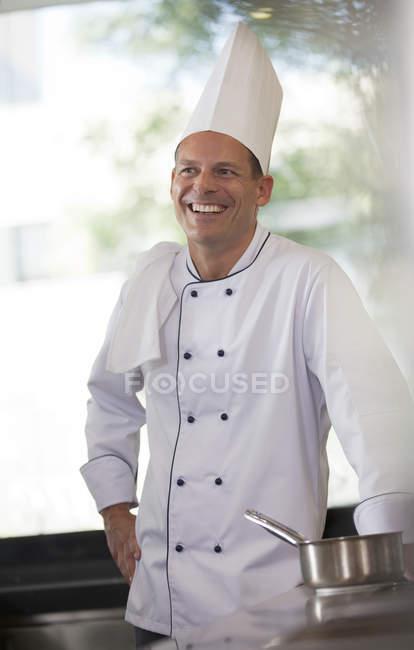 Chef smiling in restaurant kitchen — Stock Photo