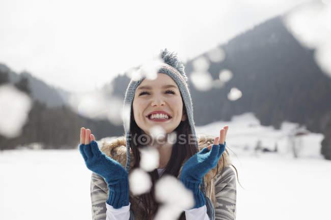 Happy woman enjoying falling snow in field — Stock Photo
