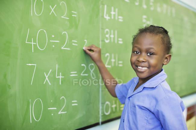 Африканский студент-американец пишет на доске в классе — стоковое фото