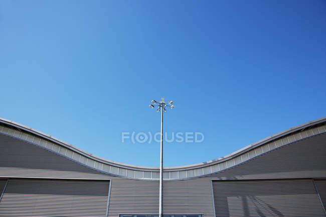 Telhado de um edifício moderno e céu azul — Fotografia de Stock