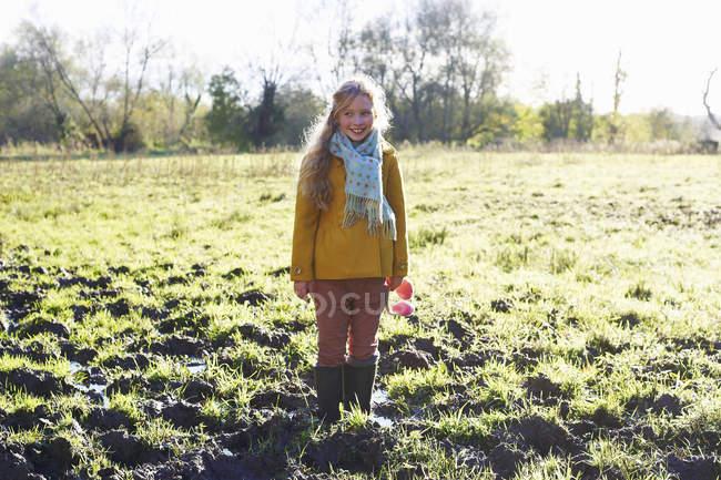 Ragazza sorridente in piedi nel campo fangoso e guardando da parte — Foto stock