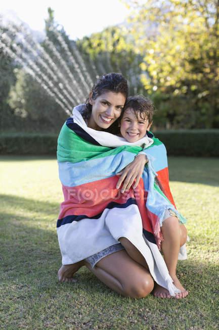 Мать и сын завернуты в полотенце на заднем дворе — стоковое фото