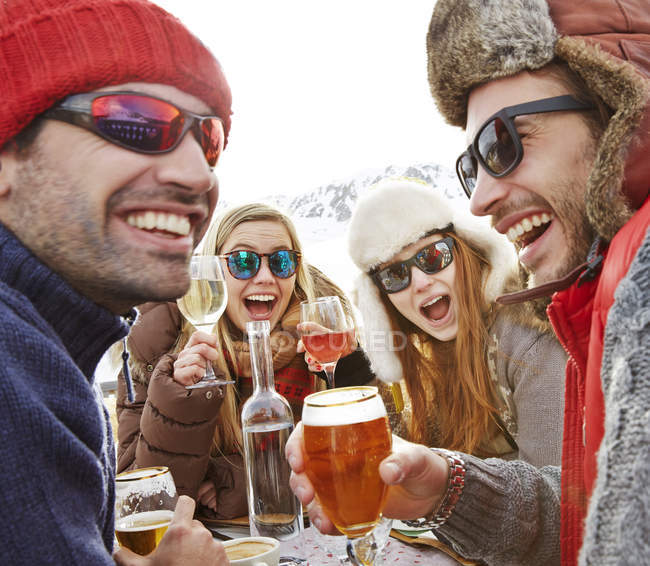 Amigos comemorando com bebidas na neve — Fotografia de Stock