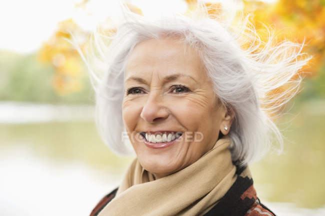 Smiling older woman standing in park — Stock Photo