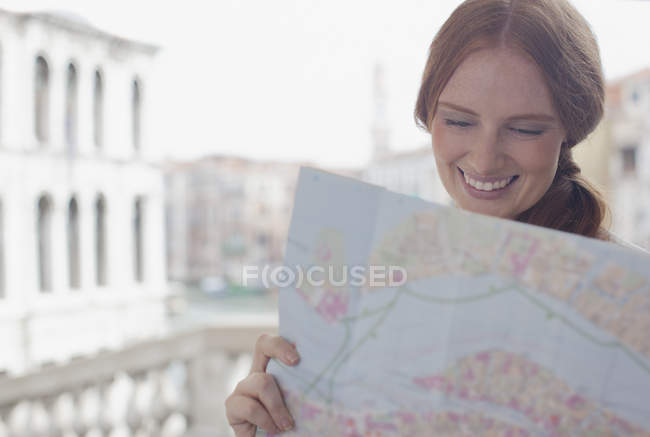 Mulher sorridente olhando para o mapa — Fotografia de Stock