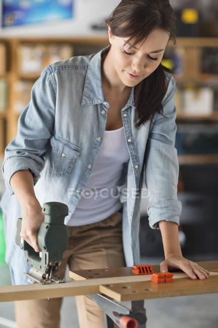 Mulher caucasiana hábil que trabalha na oficina — Fotografia de Stock