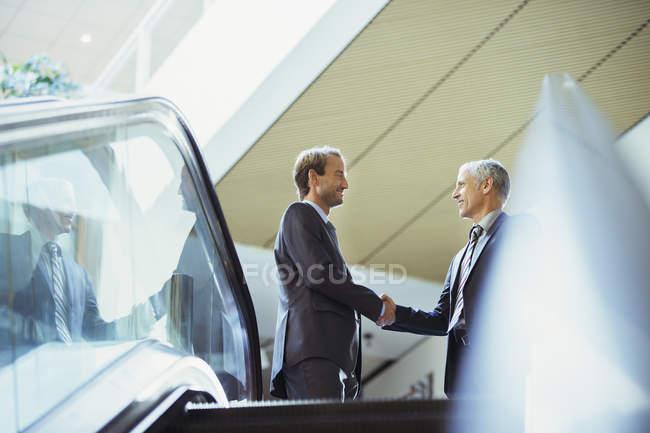 Бізнесмени рукостискань верхній частині сходи Офісна будівля — стокове фото
