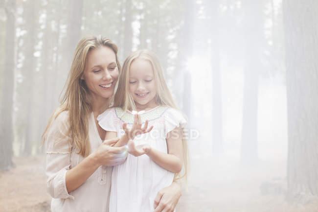 Усміхаючись, мати і дочка в Сонячний ліс — стокове фото