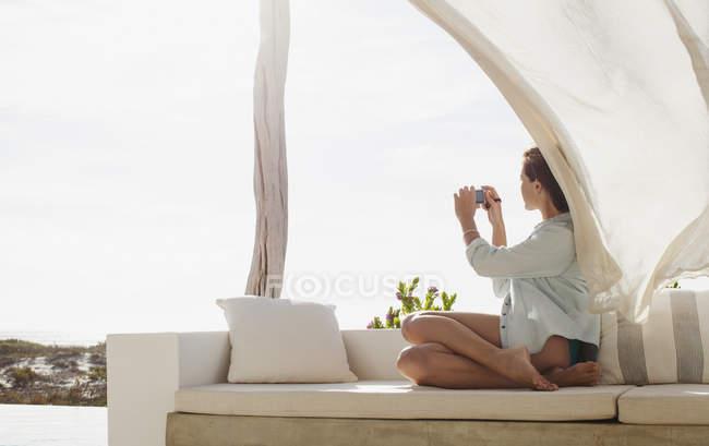 Donna che scatta foto sul patio soleggiato — Foto stock