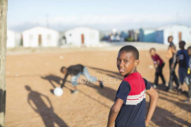 Африканские мальчики вместе играют в футбол на грязном поле — стоковое фото