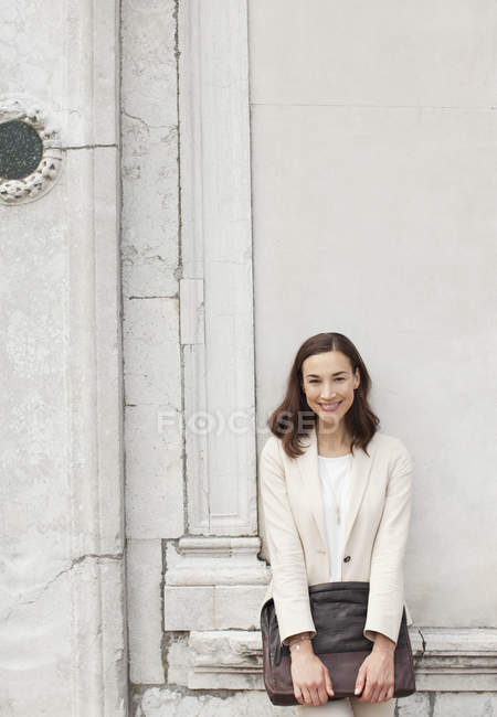 Portrait of smiling businesswoman leaning against building wall — Stock Photo