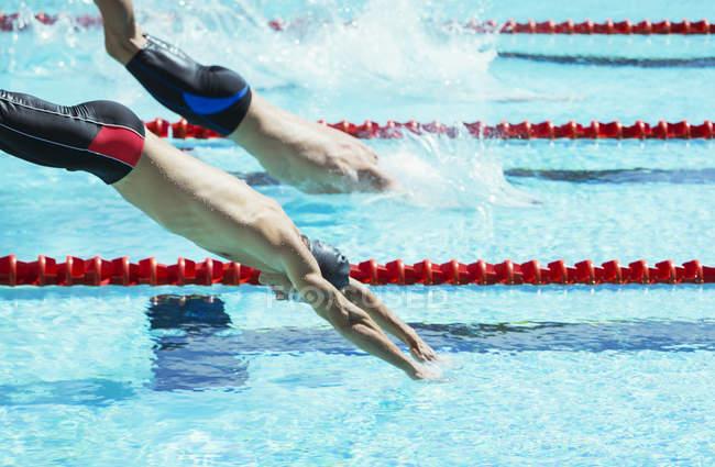 Пловцы ныряют в воду бассейна — стоковое фото