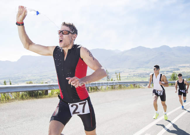 Runner se pulvériser avec de l'eau en course — Photo de stock