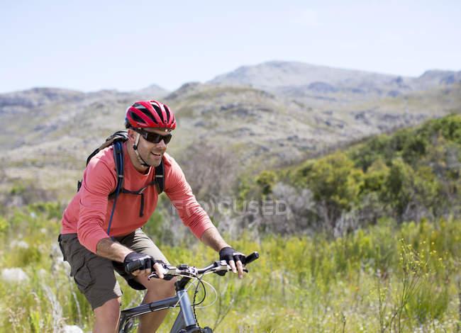 Smiling mountain biker in rural landscape — Stock Photo