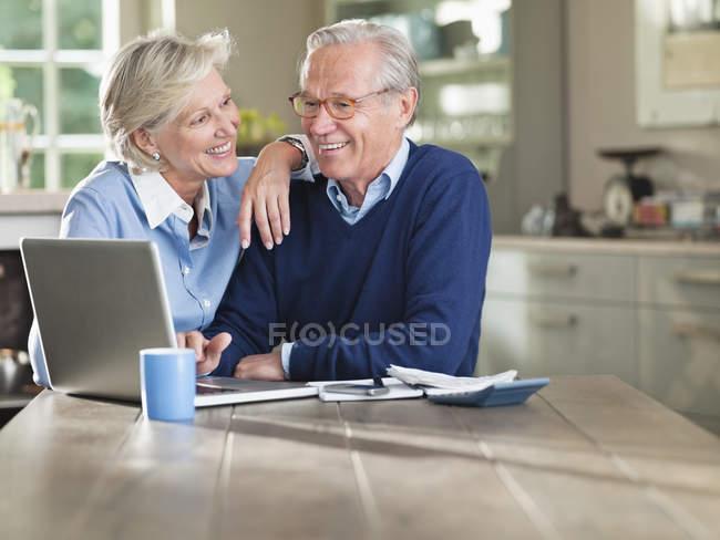 Ehepaar benutzt Laptop am Küchentisch — Stockfoto