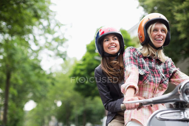 Women riding on scooter together outdoors — Stock Photo