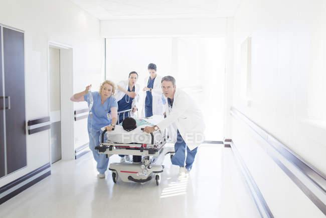Ärzte und Krankenschwestern eilen Patienten auf Trage den Krankenhausflur hinunter — Stockfoto