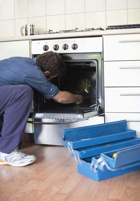 Skillful caucasian electrician working on oven in kitchen — Stock Photo