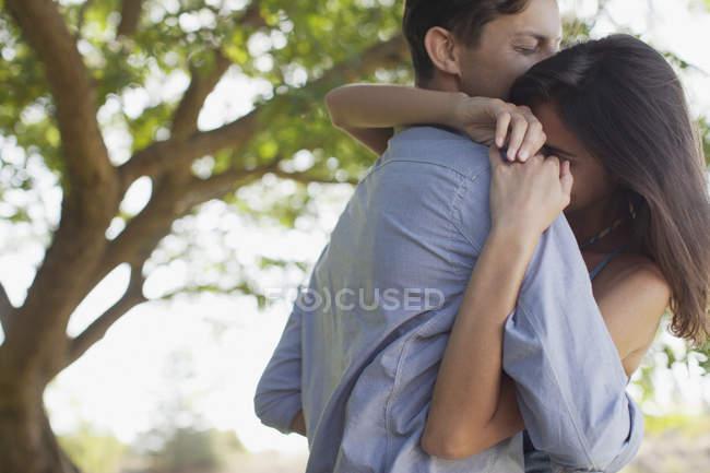 Paar umarmt sich unter Baum — Stockfoto