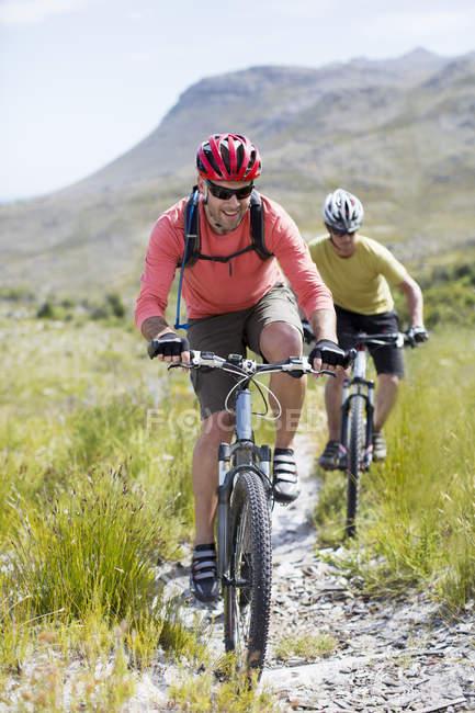 Hombres ciclistas de montaña en camino de tierra juntos - foto de stock