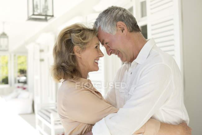 Senior caucasian couple hugging on patio — Stock Photo