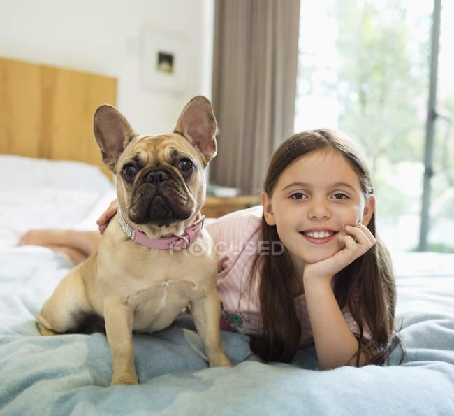 Détente avec chien sur le lit de la jeune fille souriante — Photo de stock