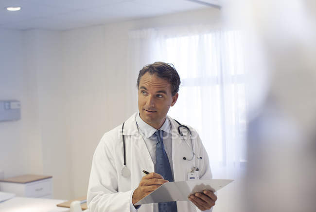 Doctor writing on clipboard in modern hospital — Stock Photo