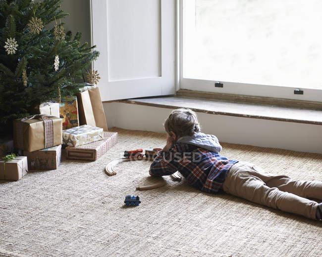 Хлопчик грає з поїздів на ялинку — стокове фото