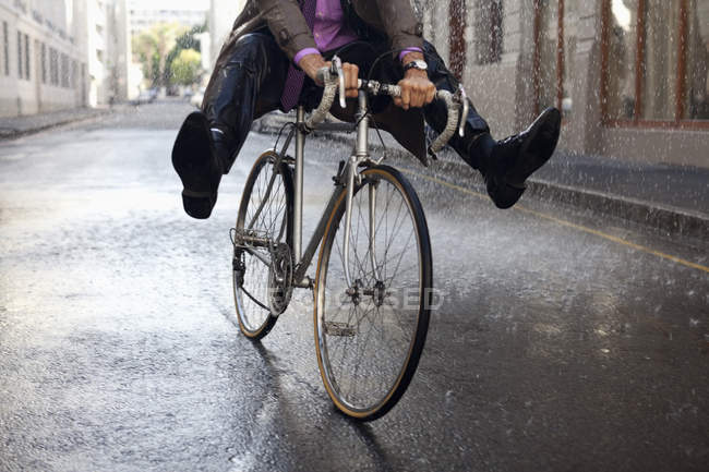Cropped image of businessman riding bicycle with feet up in rain — Stock Photo