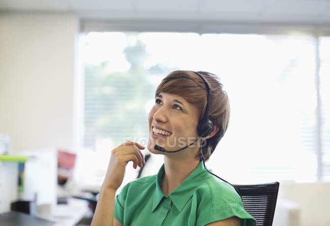 Businesswoman talking on headset at desk at modern office — Stock Photo