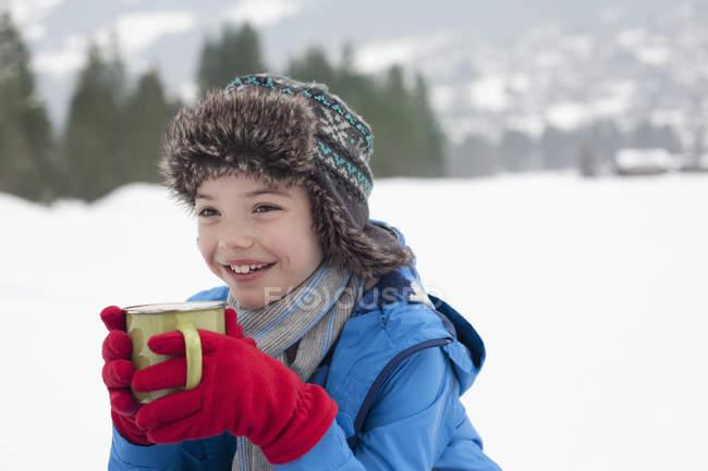 Happy boy drinking hot chocolate in snowy field — Stock Photo