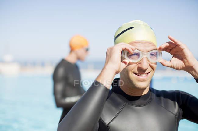 Уверенно и сильный Триатлонисты, регулируя очки на открытом воздухе — стоковое фото