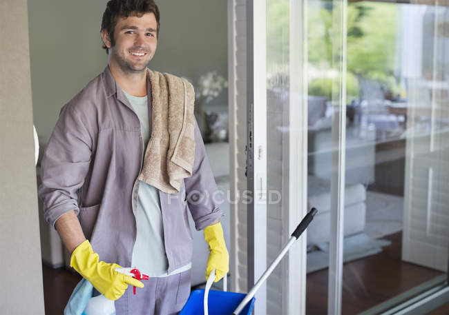 Skillful caucasian man carrying bucket of cleaning supplies — Stock Photo