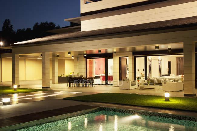 Luxury house and swimming pool illuminated at night — Stock Photo