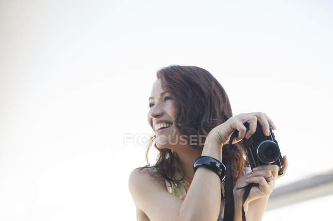 Mujer sonriente tomando fotos al aire libre - foto de stock