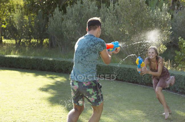 Coppia caucasica che gioca con pistole ad acqua nel cortile — Foto stock